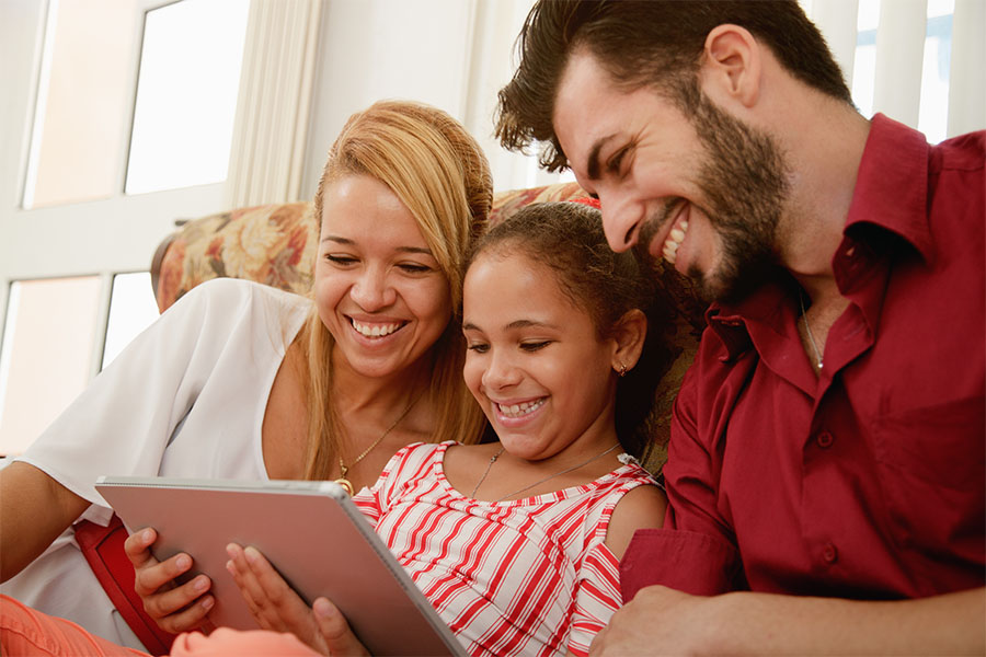 Client Center - Happy Family Sitting On Couch Using Their Tablet Together