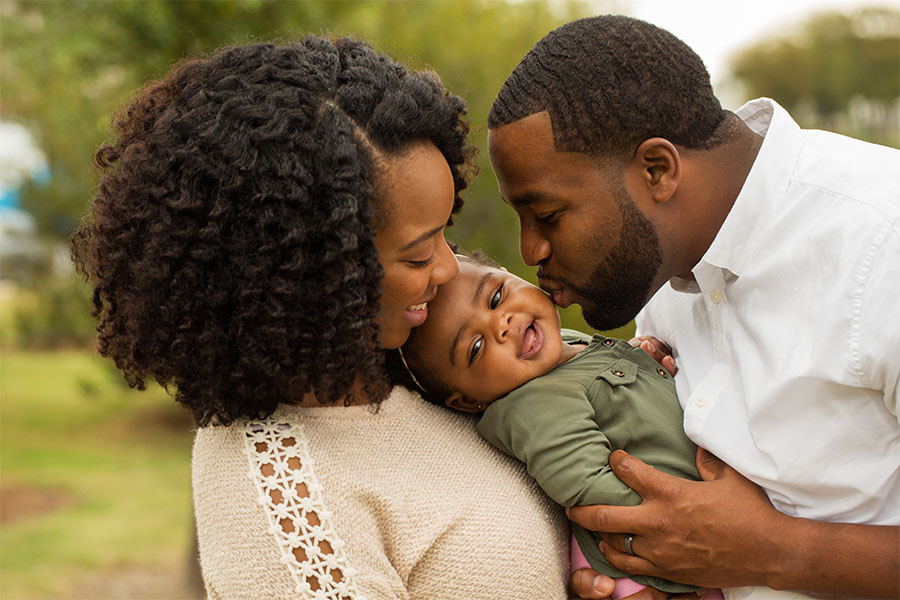 Personal Insurance - Young Parents Holding And Playing With Their Baby Outside