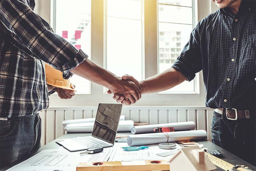 Specialized Business Insurance - Contractor And Client Shaking Hands In Office Over Desk With Building Plans